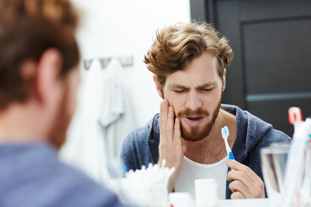 Man brushing his teeth while experiencing tooth pain.