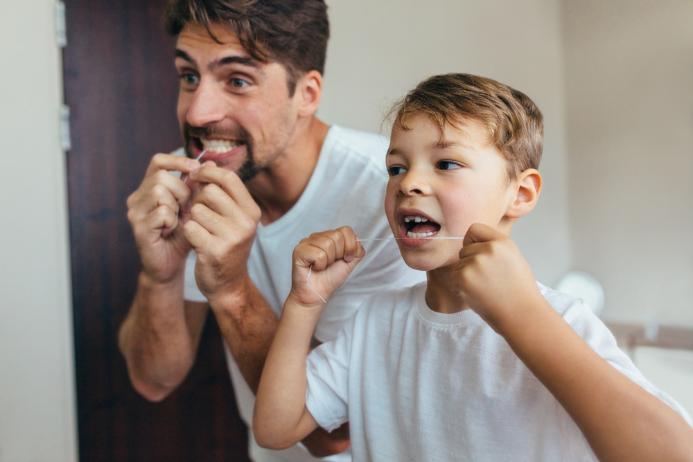 father and son flossing