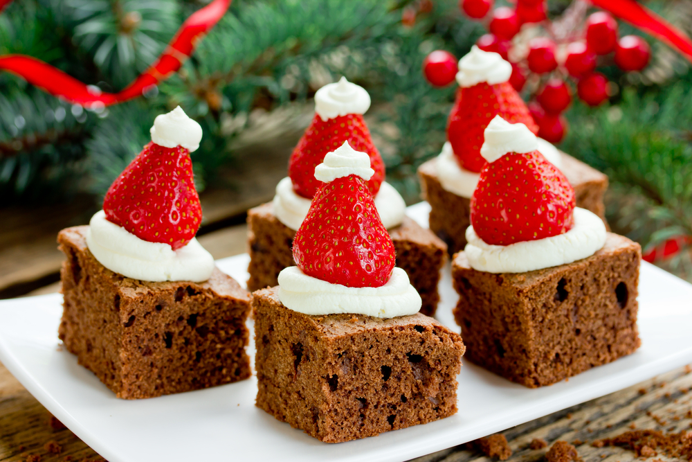 brownies with cream cheese frosting and strawberries to look like a santa hat